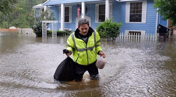 رجل يحاول عبور أحد الشوارع وسط فيضان أحد الأعاصير (اي بي ايه)