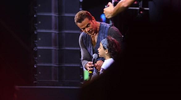 عمرو دياب يغني مع أصغر معجبيه في حفله بالساحل الشمالي (المصدر)