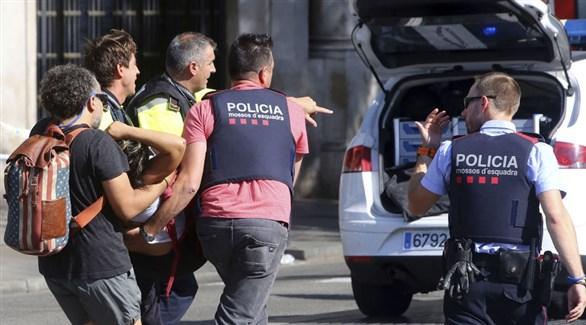 عناصر من شرطة برشلونة يسنقلون مصابة في الهجوم الإرهابي لإسعافها (أرشيف)