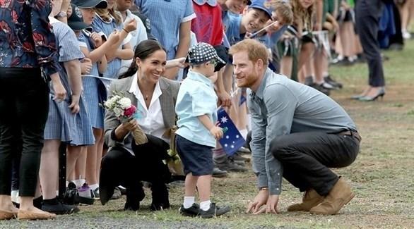 الأمير هاري وميغان ماركل يداعبان طفلاً في إحدى زياراتهما (أرشيف)