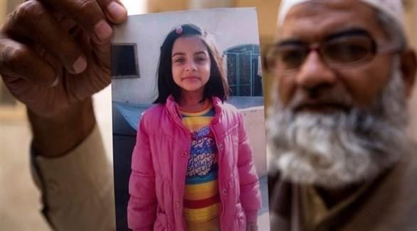 أمين أنصاري يرفع صورة ابنته زينة ضحية القاتل الباكستاني (أرشيف)