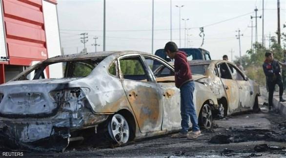 عراقيون قرب سيارات متفحمة بعد انفجارها في عملية سابقة (رويترز)