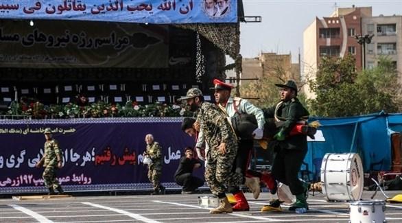 عسكريون إيرانيون يُجلون جريحاً بعد الهجوم على العرض في الأحواز (أرشيف)