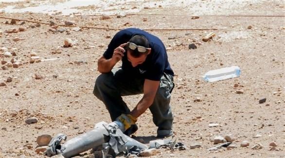 إسرائيلي يُعاين شظايا قذيفة سابقة أطلقت من غزة (أرشيف)