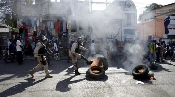 عناصر من مكافحة الشغب في هايتي يحاولون إطفاء إطارات محترقة في احتجاجات أمس (إر إف أي)