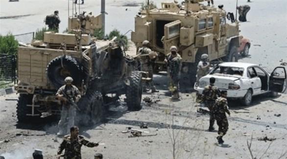 مدرعات تابعة لقوات ناتو وجنود في أفغانستان إلى جانب سيارة مدمرة (أرشيف)