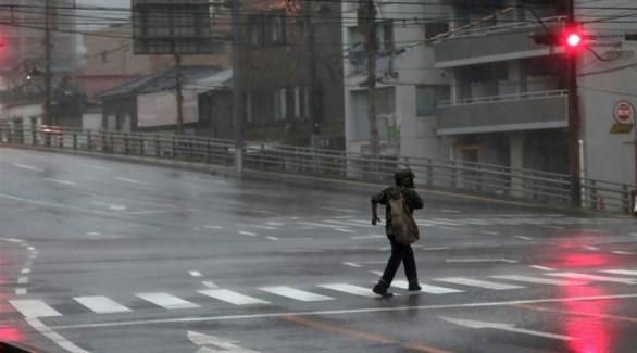 ياباني يحاول قطع الشارع في ظل الإعصار ترامي (أ ف ب)