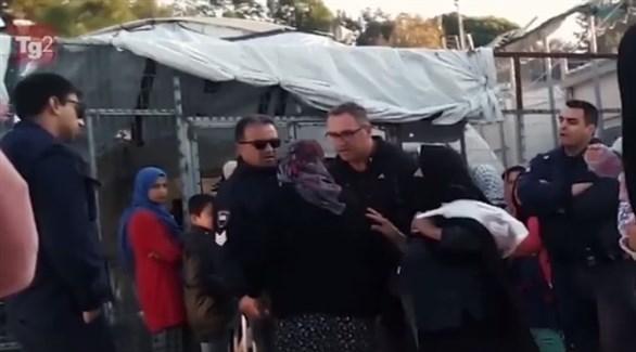 صورة من مقطع فيديو يظهر ضابط يوناني يهين لاجئة مسنة في مخيم موريا (تويتر)