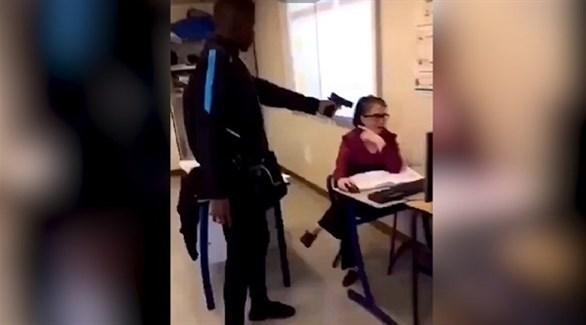الطالب مُشهراً مسدسه في وجه معلمته (يوتيوب)