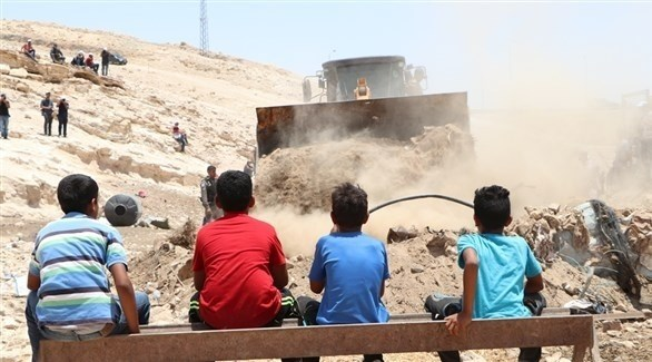 أطفال فلسطينيون من الخان الأحمر يراقبون هدم جرافات الاحتلال لمساكنهم (أرشيف)