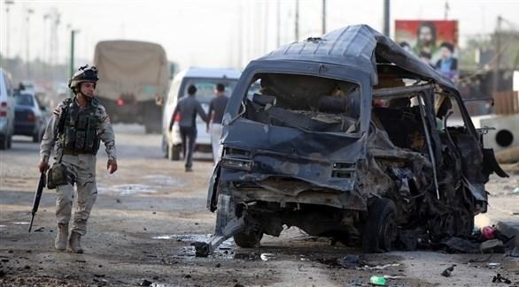 جندي عراقي أمام سيارة تفحمت بعد تفجير سابق (أرشيف)