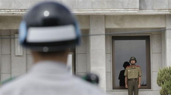جندي من كوريا الشمالية وآخر من كوريا الجنوبية على الحدود بين البلدين (أرشيف)
