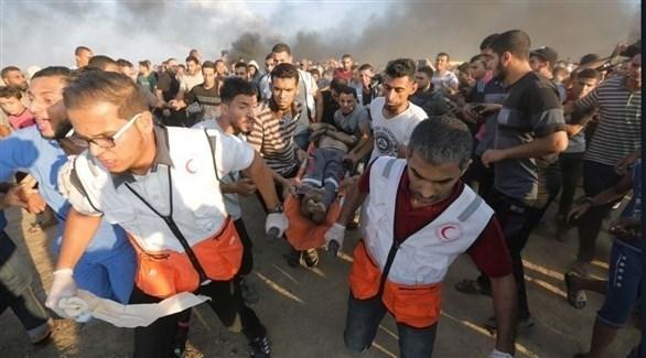 مسعفون ينقلون فلسطينياً أصيب خلال مسيرات العودة بغزة (أرشيف)