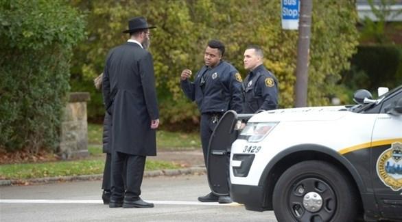 شرطيان أمريكيان يتحدثان إلى يهودي في محيط الكنيس المستهدف في بنسلفانيا (أ ف ب)