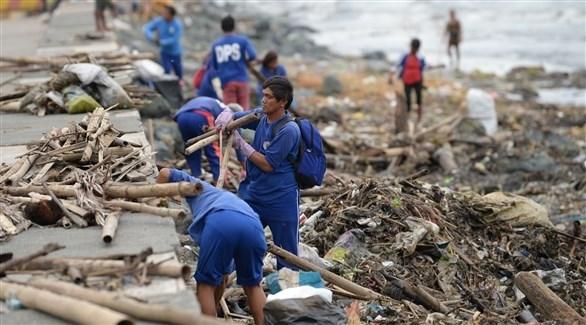 عمال في مانيلا يجمعون مخلفات إعصار يوتو  (أ ب)
