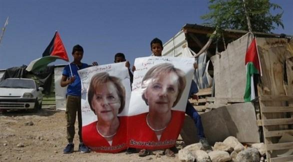 أطفال في قرية الخان الأحمر يحملون صورة ميركل (تويتر)