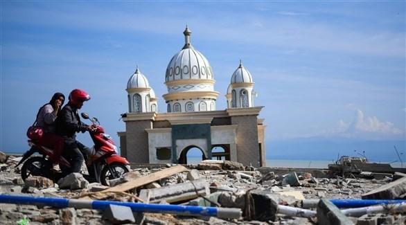 رجل وامرأة على دراجة نارية وسط الأنقاض بعد زلزال إندونيسيا (أ ف ب)