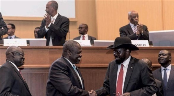 رئيس جنوب السودان سلفا كير ونائبه السابق رياك مشار في مصافحة قبل توقيع اتفاق السلام في أديس أبابا (أرشيف)
