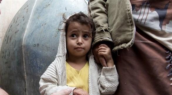 طفل يني بجانب أحد أفراد عائلته (الأمم المتحدة)