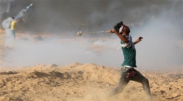متظاهر فلسطيني يستعد لرمي حجارة على جنود الاحتلال (رويترز)