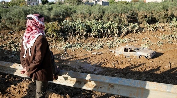 رجل ينظر إلى سيارة جرفتها السيول في الأردن (اي بي ايه)