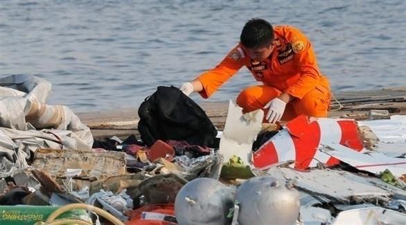عنصر من فرق الطوارئ يجمع ما بقي من أمتعة كانت على الطائرة المنكوبة (أرشيف)