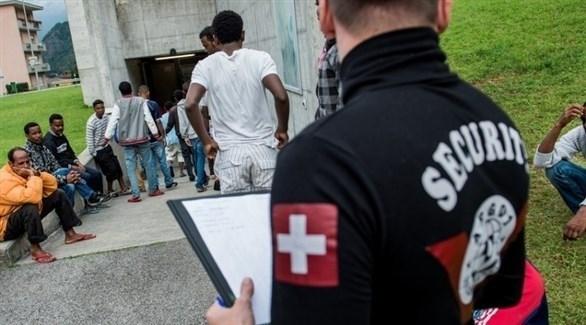 شرطي سويسري يراقب مجموعة من المهاجرين (أرشيف)
