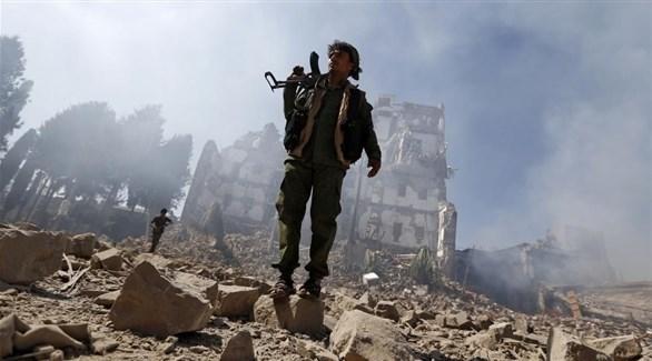 مسلح في اليمن يقف فوق ركام جراء المعارك