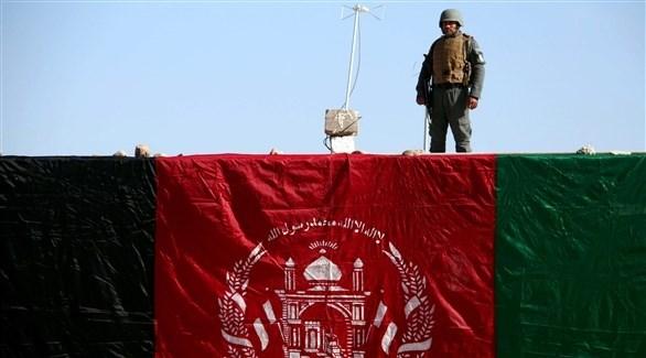 جندي يقف بجانب العالم الأفغاني (اي بي ايه)