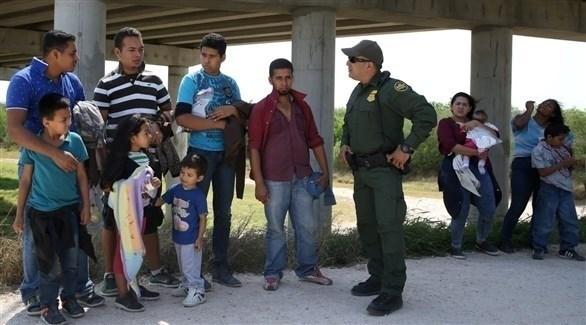 عنصر من حرس الحدود الأمريكي مع مهاجرين غير شرعيين قادمين من المكسيك (أرشيف)