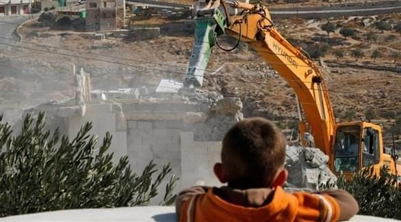طفل يشاهد آلية إسرائيلية تهدم منزلاً