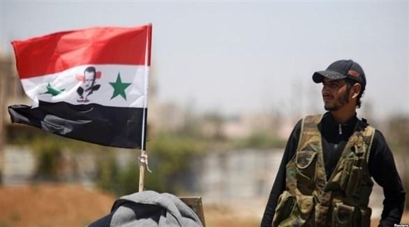مجند بالقرب من علم سوريا ويظهر وجه بشار الأسد عليه (أرشيف)
