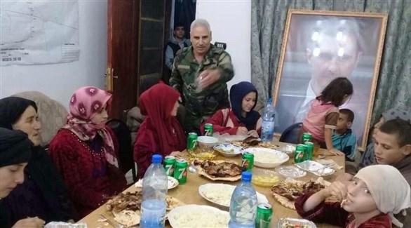 ضابط سوري بجانبه صورة للأسد أمام مائدة للمحررين من داعش (سانا)