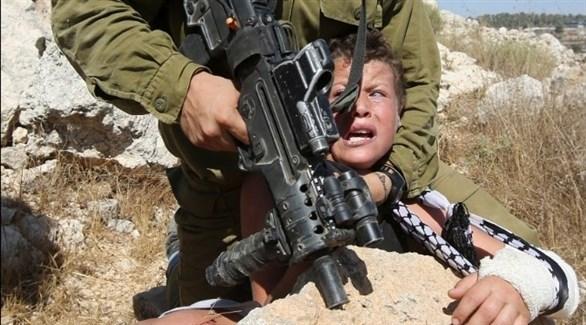 عنصر من جيش الاحتلال تعتلق طفلاً (أرشيف)