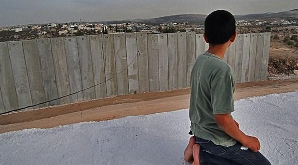 طفل فلسطيني على ركبتيه عند الجدار الفاصل في الضفة الغربية (أرشيف)