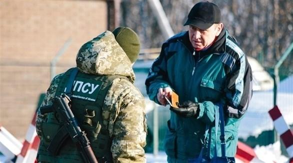 أحد حراس الحدود الأوكرانيين يتفحص وثائق رجل سيعبر الحدود إلى روسيا عند نقطة التفتيش على الحدود مع روسيا (AP)