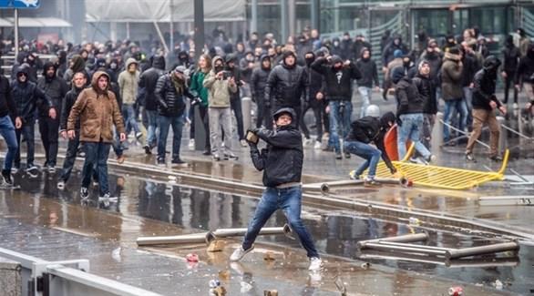 متظاهر يرمي رجال الأمن بحجر في بروكسل (بلغا)