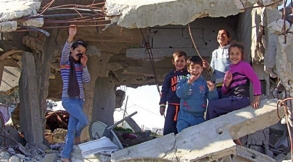 أطفال من غزة يقفون على أنقاض مبنى مدمر (أرشيف)