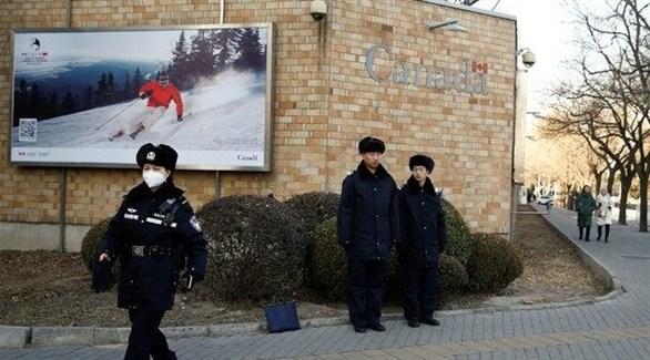 عناصر من الشرطة الصينية أمام السفارة الكندية