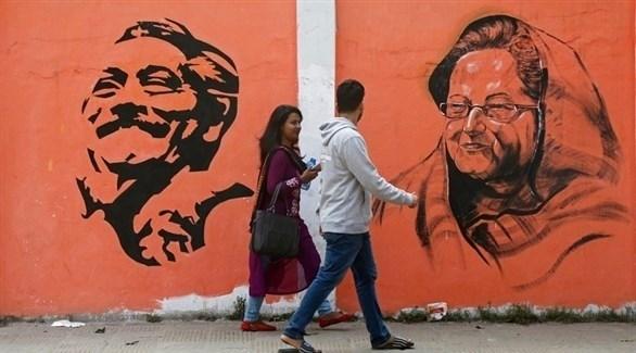 أشخاص يسيرون أمام لوحة انتخابية في بنغلاديش (إ ب أ)