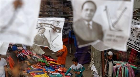 أشخاص يتجولون في أحد الأسواق ويظهر يافطات انتخابية معلقة (أ ف ب)