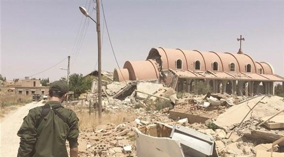 مسلح كردي أمام أنقاض كنيسة السيدة مريم العذراء في تل نصري التي دمرها داعش (أرشيف)