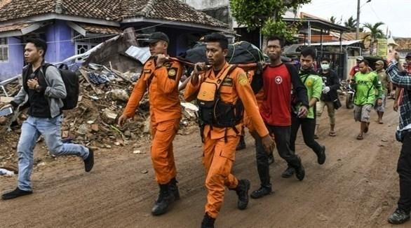 منقذون يحملون جثة أحد ضحايا تسونامي إندونيسيا (أ ف ب)