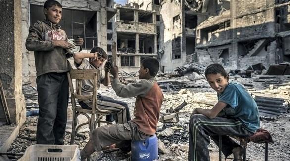 أطفال سوريون جالسون على أنقاض مبنى مدمر (أرشيف)