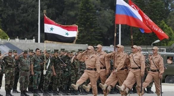 قوات روسية تمر بجانب قوات سوريا (أرشيف)