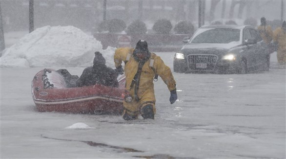 رجل إنقاذ يساعد في إخراج رجل آخر من وسط الثلوج (أرشيف)