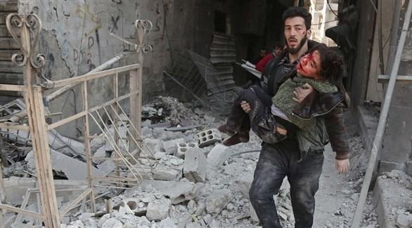 سوري يحاول إنقاذ طفلة أصيبت بالقصف (أرشيف)