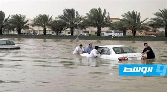 ليبيون يحاولون إخراج سيارة غرقت في المياه (بوابة الوسط)