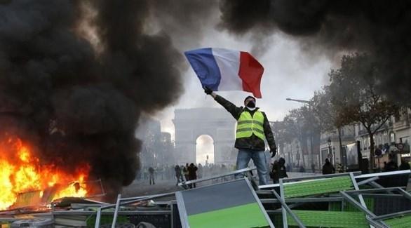 محتج من السترات الصفراء يرفع العلم الفرنسي أمام قوس النصر في باريس (أرشيف)