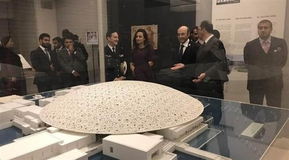 زكي نسيبة وبعض المشاركين في الاحتفال أمام مُجسم متحف اللوفر أبوظبي في لوفر باريس (من المصدر)
